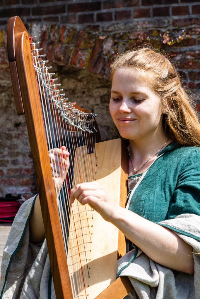Cathinca die op de harp speelt